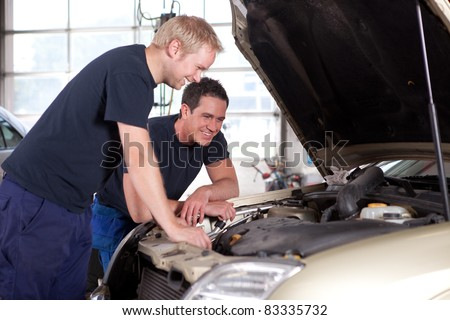 Two man mechanics smiling and working under the hood of a car, shallow depth of field, sharp focus on rear mechanic - stock photo