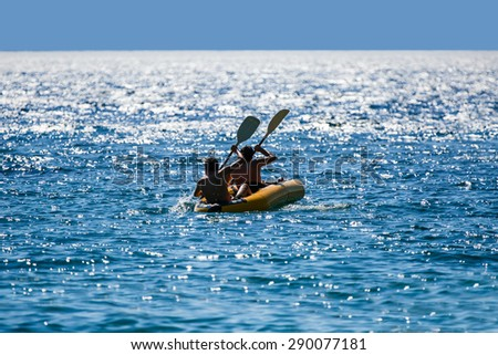 two man paddles a rubber boat on the sea - stock photo
