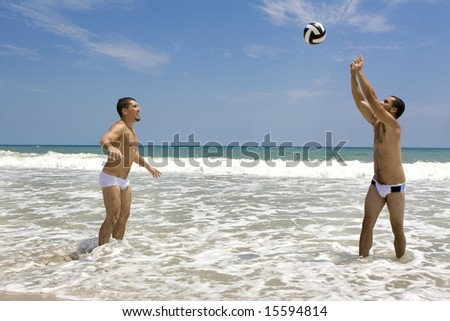 Two man playing volleyball at the beach - stock photo