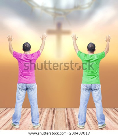 Two man raising hands on wooden paving over blurred crown of thorns and the cross on a sunset.  - stock photo
