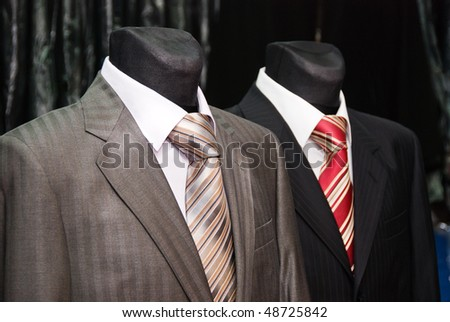 two man's business suit and ties on a dummy