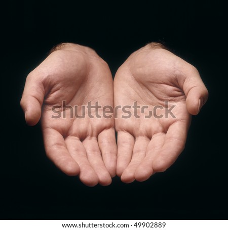 Two man's hands in offering gesture against black background