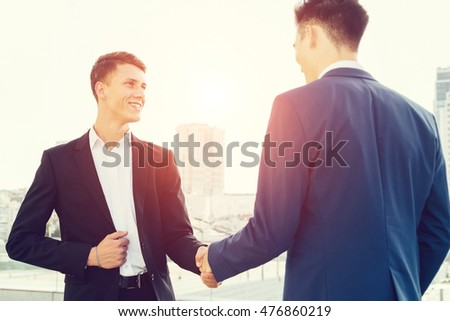 Two man shaking hands. Business people shaking hands, finishing up a meeting. Close up people.