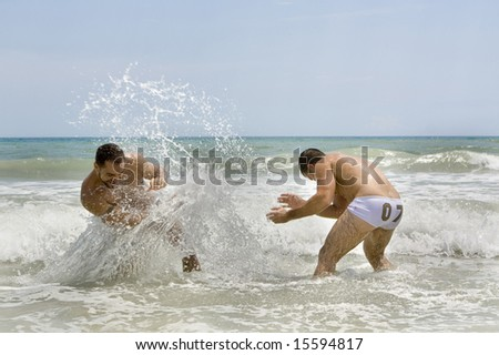 Two man splashing water in the ocean - stock photo