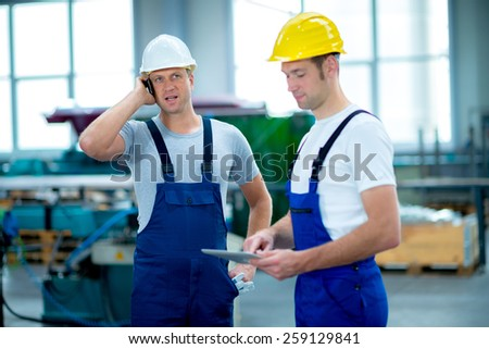 two man together in factory with tablet PC and cellphone - stock photo