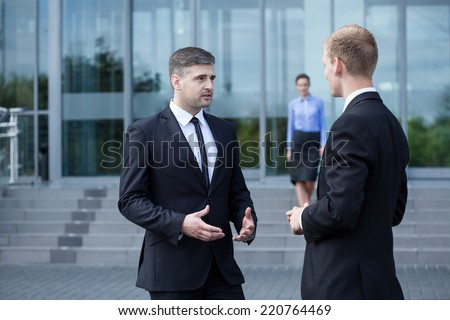 Two man wearing formal clothing talking in front of the building
