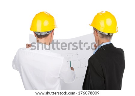 two man wearing yellow helmets. back view of workers talking about plan - stock photo