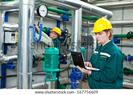 Two man working in a factory, controls the operation of devices in a Heating Plant or Refinery. Please see my other photo and videos with the same theme.  - stock photo