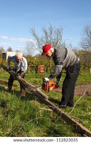 two man working in garden. destroy old building and sawing planks. - stock photo