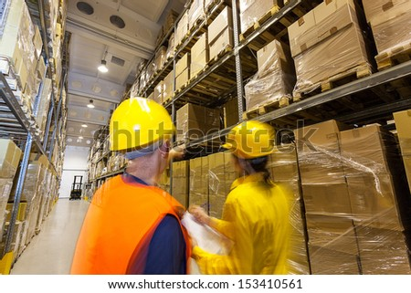 Two managers checking products in huge warehouse - stock photo
