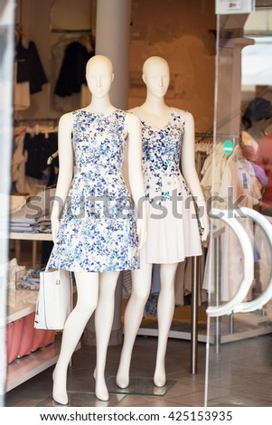 Two mannequins in summer dresses at the store entrance - stock photo