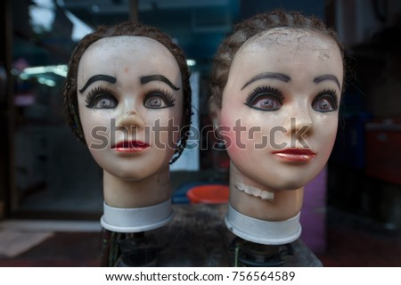 Two mannequins of a woman: female heads on the cheek stand on the stand, faces are covered with cosmetics.