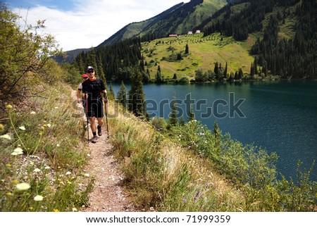 Two mans on the trail along Kolsai lake, Kazakhstan - stock photo