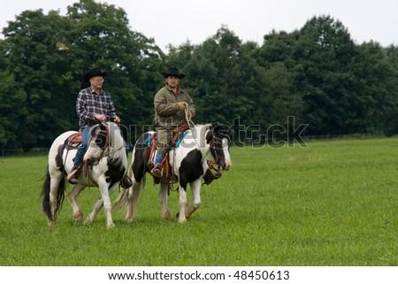 Two mans riding irish cob herses - stock photo