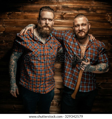 Two mans with beards and tattoo posing over wooden wall. One of them holding axe. - stock photo