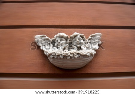 Two marble angels on the wall - exterior - stock photo