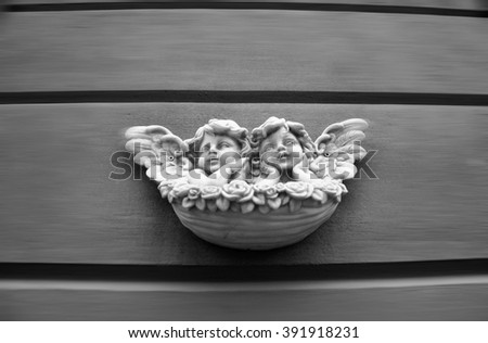 Two marble angels on the wall - exterior - black and white picture - stock photo