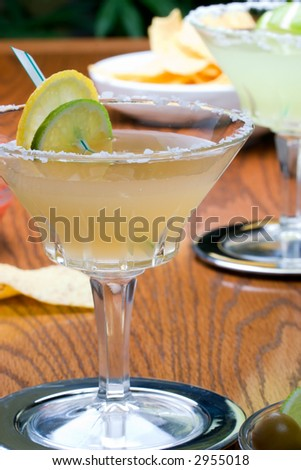 Two margarita cocktail  - Golden Margarita, Midori Margarita - glasses and tortilla chips on party table - stock photo