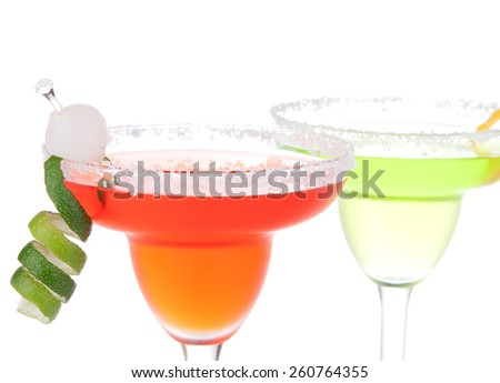 Two Margarita cocktails yellow and res with mint and lime spiral in chilled salt rimmed glass with tequila orange syrup crushed ice in cocktails glass isolated on white background - stock photo