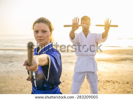 Two martial arts athletes training with weapons on the beach at sunrise - Sportive man and woman with stick and nunchaku - Kung fu and karate masters - stock photo