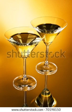 Two martini glasses on yellow background