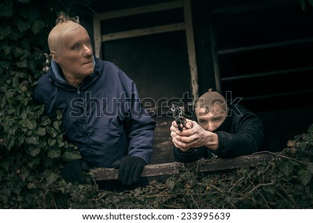 Two masked armed men hiding on overgrown porch of old cabin. - stock photo