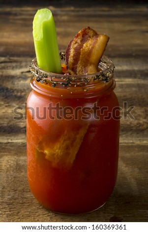 Two mason jar Bloody Mary or Caesar  with  bacon  on wood background - stock photo