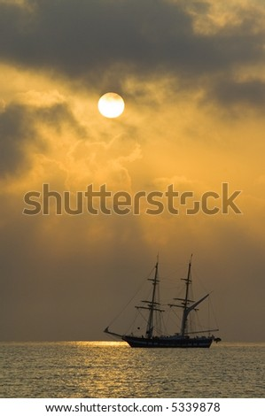 Two-masted sailing boat against a dramatic golden dawn or sunset cloudscape on calm water