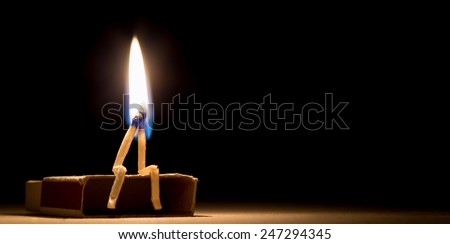 Two matches burning sitting together on the matchbox in the dark copy space. Two matches in flame as a metaphor of togetherness friendship and love - stock photo