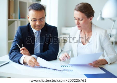 Two mature business partners discussing documents in office
