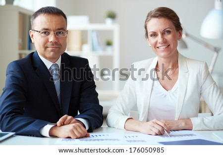 Two mature business partners looking at camera in office - stock photo