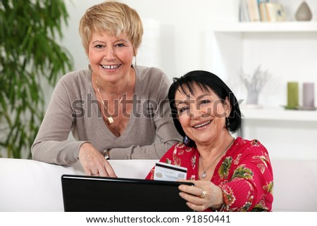 Two mature female friends shopping online.