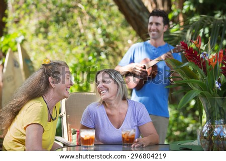 Two mature happy women with ukelele player - stock photo