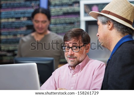 Two mature men talking in a coffee house