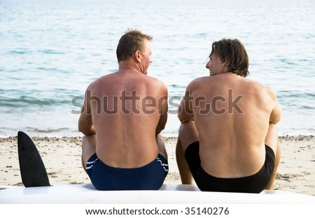 Two mature sporty men sitting on beach and chatting. - stock photo