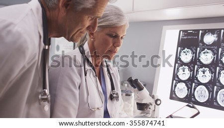 Two mature white scientists reading a tablet - stock photo