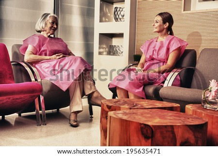 Two mature women patient talking in the hospital waiting room.