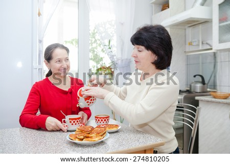 Two mature women talking over coffee in   kitchen. - stock photo