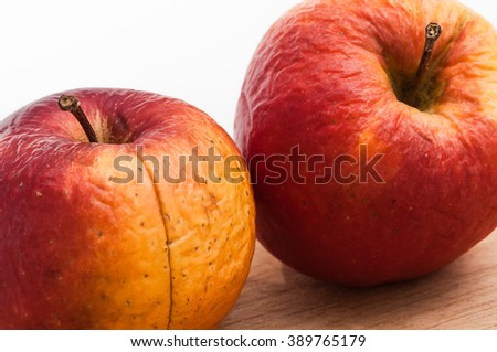 Two matured and crumpled apples on wooden board against white background; Grow old together - stock photo