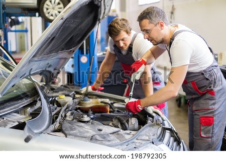 Two mechanic fixing car in a workshop - stock photo
