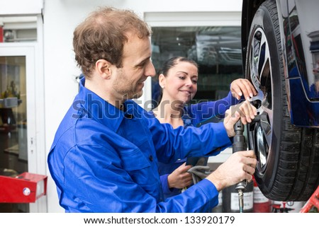 Two mechanics changing a wheel on a car standing on a hydraulic ramp - stock photo