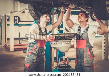 Two mechanics changing oil  in a car workshop - stock photo