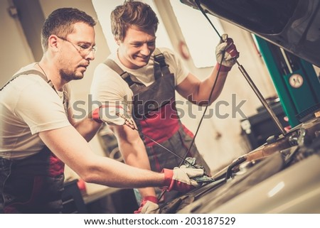 Two mechanics checking oil level in a car workshop - stock photo