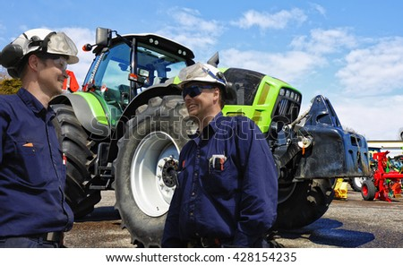 two mechanics, farmers with large tractors in background - stock photo