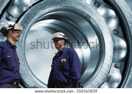 two mechanics in front of a giant ball-bearing, steel works - stock photo