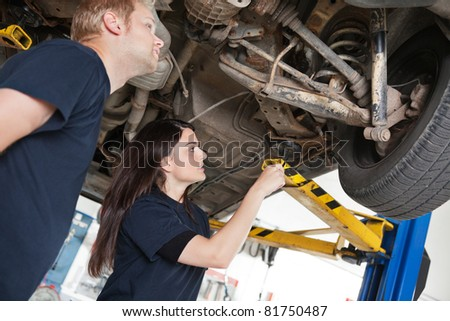 Two mechanics looking at a car discussing a problem - stock photo