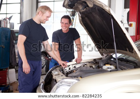 Two mechanics looking at and working on a car in a repair shop - stock photo
