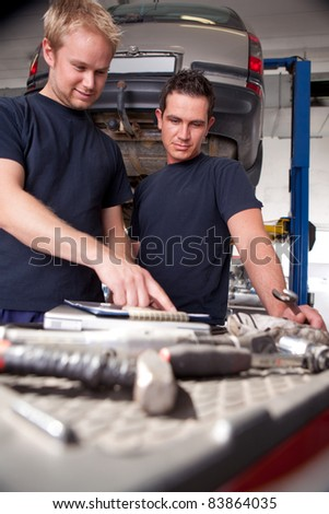 Two mechanics looking at work order and discussing repairs - stock photo