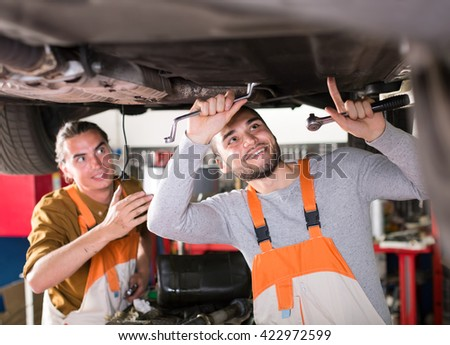 Two mechanics repairing a car with a wrench from the bottom at a automobile repair workshop - stock photo