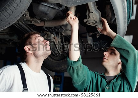Two mechanics repairing car in garage under the car. - stock photo